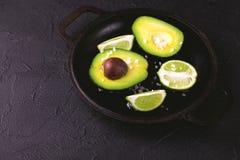 Авокадо, куски соли моря и известки на каменной предпосылке Стоковые Фото