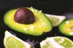 Авокадо, куски соли моря и известки на каменной предпосылке Стоковое Изображение
