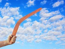 Австралийский бумеранг в руке людей против пасмурного голубого неба Стоковая Фотография