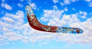 Австралийский бумеранг летает в небо против чисто белых облаков Стоковые Фото