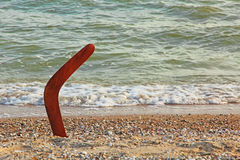 Австралийский бумеранг на песочной береговой линии около прибоя моря Стоковые Изображения RF