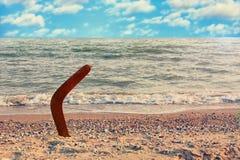 Австралийский бумеранг на песочной береговой линии против волны и неба моря Стоковое Изображение RF