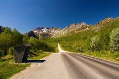 Автобусная остановка на главной дороге окруженной красивыми горами, Норвегии Lofoten стоковое изображение