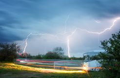 автобус в сельской местности управляя против фона бурных неба и молнии стоковые изображения rf