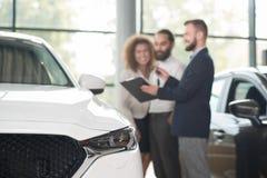 Автодилер обсуждая приобретение автомобиля с клиентами стоковая фотография rf