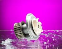 Автозапчасти, насос двигателя охлаждая в спуртах воды на фиолетовом bac Стоковые Изображения