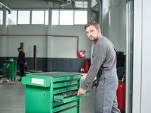 Автоматический механик принимает инструмент от зеленой резцовой коробки indoors стоковая фотография rf