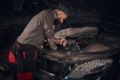 Автоматический механик проверяет двигатель автомобиля во время ремонта в гараже Стоковые Фото