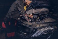 Автоматический механик проверяет двигатель автомобиля во время ремонта в гараже Стоковое Изображение