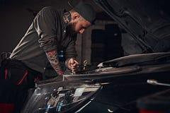 Автоматический механик проверяет двигатель автомобиля во время ремонта в гараже Стоковые Изображения