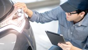 Автоматический механик проверяя фару автомобиля используя планшет стоковое изображение rf
