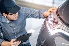 Автоматический механик проверяя фару автомобиля используя таблетку стоковая фотография rf