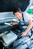 Автоматический механик работая в обслуживании автомобиля Стоковые Изображения