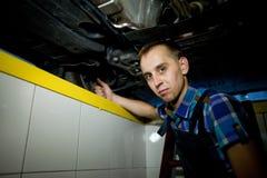 Автоматический механик работая под поднятым автомобилем Стоковые Фото
