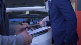 Автоматический техник пишет назначения от клиента об осмотре и ремонте автомобиля с клобуком открытым на мастерской сток-видео