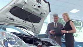 Автоматический торговец показывая мотор электрического автомобиля к молодой женщине акции видеоматериалы
