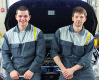 2 автоматических механика рассматривая автомобиль с открытым клобуком Стоковое Изображение