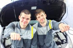 2 автоматических механика рассматривая автомобиль с открытым клобуком Стоковые Фотографии RF