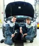 2 автоматических механика рассматривая автомобиль с открытым клобуком Стоковые Фото