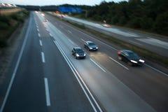 Автомобили быстро проходя на шоссе в вечере Стоковые Фото