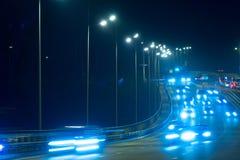 Автомобили движения шоссе на blured ноче Автомобили двигая дальше дорогу на bri Стоковые Изображения