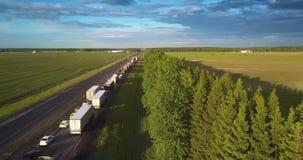 Автомобили длиной гребут в правой майне вдоль трассы среди ландшафта акции видеоматериалы