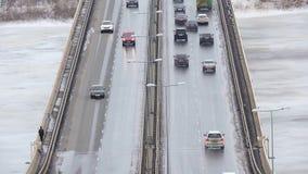 Автомобили ездят по снегоходной дороге зимой, движение по мосту, шоссе