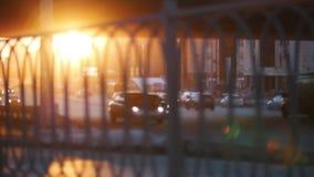 Автомобили ехать на дороге на заходе солнца Взгляд через несосредоточенное обнесет забором передний план сток-видео