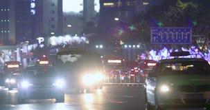 Автомобили идут вечером в дождь, фары проблескивают в рамке Движение ночи в большом городе акции видеоматериалы