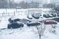 Автомобили на автостоянке около жилого дома покрытого снегом Стоковая Фотография RF