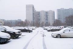 Автомобили на автостоянке около жилого дома покрытого снегом Стоковые Изображения RF