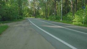 Автомобили на дороге с улицей подписывают внутри лес сток-видео