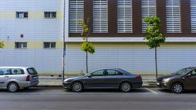 Автомобили припарковали на дороге против предпосылки нового городского здания стоковые фотографии rf