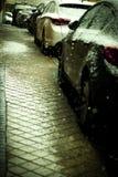 Автомобили припарковали на улице пока она идет снег Стоковая Фотография