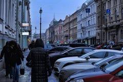 Автомобили припаркованные на улице в центре города и пешеходах стоковые изображения rf