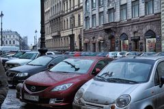 Автомобили припаркованные на улице в центре города и пешеходах стоковое изображение rf