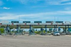Автомобили пропуская через платные ворота на шоссе Стоковая Фотография