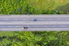 Автомобили пропуская через сельскохозяйственные угодья окруженные платной дорогой стоковое изображение