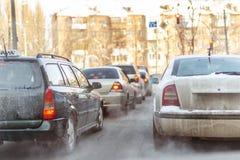 Автомобили стоя в строке в заторе движения на улице города на скользкой снежной дороге в зиме Корабли получают вставленными на до стоковое фото