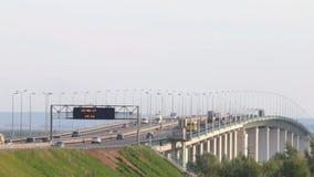 Автомобили, шины и тележки двигают на современный мост с табельной доской сток-видео