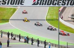 автомобили 1 обходят вокруг участвовать в гонке gra формулы Стоковое фото RF
