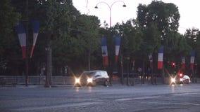 Автомобильное движение Парижа городское на бульваре Champs-Elysees в свете crepuscle