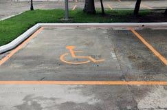 Автомобиль автостоянки неработающего, оранжевого плана человека с кресло-каталкой на поле стоковая фотография