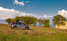 Автомобиль в луге с деревьями и голубым небом позади стоковые фотографии rf