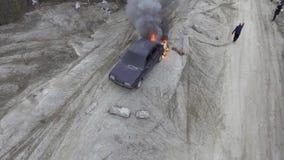 Автомобиль горит с большим пламенем в дезертированном поле пыли окруженном пустыми деревьями акции видеоматериалы