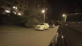 Автомобиль двигает вдоль улицы города на ночи лета акции видеоматериалы