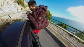 Автомобиль двигая быстрое вниз шоссе, выходить парня переднего окна сиденья пассажира видеоматериал