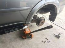 Автомобиль для того чтобы извлечь колесо для обслуживания с оборудованием подъемной силы создаваемая корпусом стоковые изображения