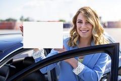 Автомобиль женщины готовя держа белый пустой плакат Стоковое фото RF
