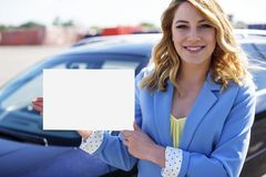 Автомобиль женщины готовя держа белый пустой плакат Стоковые Фотографии RF